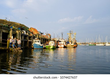 SCARBOROUGH, ENGLAND - APRIL 21: A family crabbing in Scarborough harbour on a beautiful warm evening. In Scarborough, England. On 21st April 2018.
