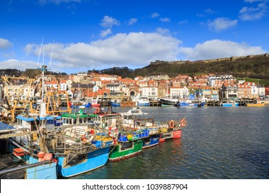 SCARBOROUGH, ENGLAND - FEBRUARY 24: Colourful fishing boats in Scarborough harbour on a sunny Winter morning. In Scarborough, England. On 24th February 2018.