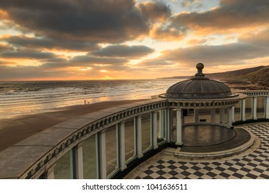 SCARBOROUGH, ENGLAND - FEBRUARY 24: Person walking dog on beach as sun rises over Scarborough Spa bandstand. In Scarborough, England. On 24th February 2018.