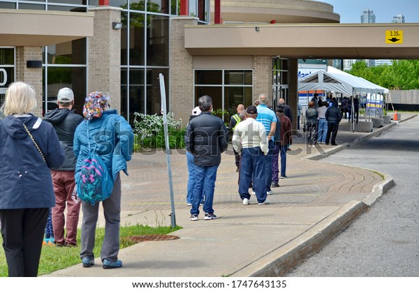 Scarborough, Ontario, Canada, June 2, 2020: People wait in line for a Covid-19 test at the pop-up mobile Assessment Centre at 1250 Markham Road in Scarborough, Ontario.