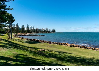 Scarborough, Queensland, Australia - 10/22/2019:the Scarborough beach and water front with a calm Moreton bay at low tide with a clear afternoon sky and scattered clouds in the background