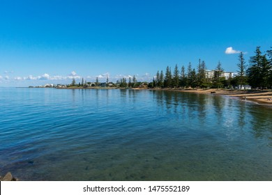 Scarborough, Queensland, Australia - 8/5/2019: the Scarborough beach front at low tide with a calm moreton bay and the Redcliffe jetty and shops in the background and a clear afternoon sky above