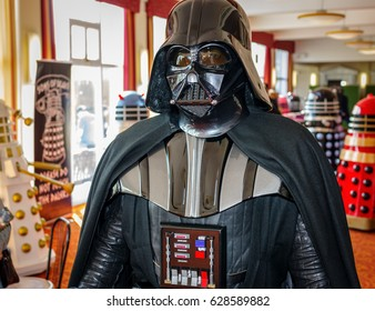 Scarborough, UK - April 08, 2017: 'Darth Vader' from 'Star Wars' walks through hall at Sci-Fi Scarborough with 'daleks' from 'Doctor Who' in the background.