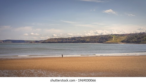 Scarborough, UK.  April 30, 2021.  Waves roll towards a beach and a headland stretches out towards the horizon. A path winds its way down to the beach and a sky with clouds is above.
