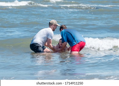 SCARBOROUGH, UK – JULY 1, 2018: Church leaders baptise a girl child by full immersion in the North Sea (public baptism)
