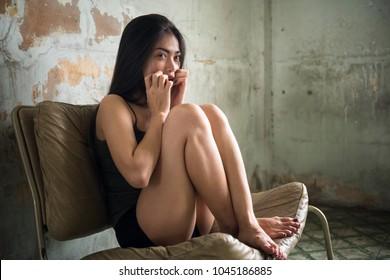 Scare crazy beautiful Asian girl sitting on seat in abandon house. Mental psychosis sickness after being rape and hostage in dirty bedroom. Social issue concept for female safety life.