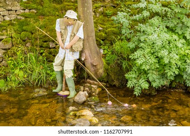 Scarecrow at Scarecrow Festival in North Yorkshire, England.  Portraying a man fly fishing in a river with rod and line. Horizontal