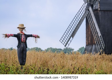 Scarecrow in front of wooden traditional post mill from late 18th century in Olsztynek heritage park in Masuria region of Poland