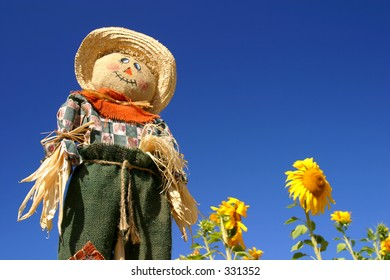 A scarecrow stands tall over a sunflower forest.