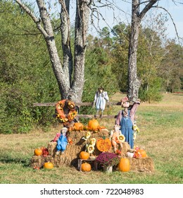 Scarecrow, yellow mum flowers, harvested orange pumpkins, squashes, gourd over hays in rural Arkansas, USA. Scarecrow guarding pumpkin from birds. Traditional Halloween, Thanksgiving, Fall decoration