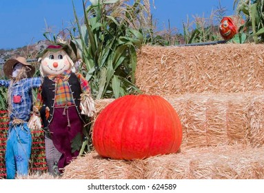 Scarecrows Standing Beside Giant Pumpkin On Bales Of Straw