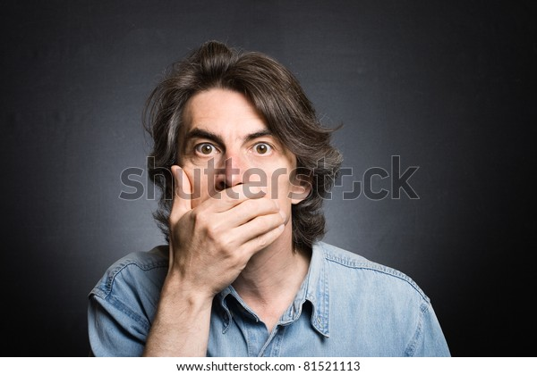 scared adult man with hand covering mouth and dramatic lighting