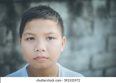 scared and alone, young Asian child who is at high risk of being bullied, trafficked and abused. Selective focus