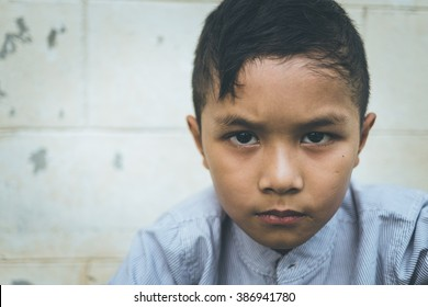 scared and alone, young homeless Asian child who is at high risk of being bullied, trafficked and abused, selective focus