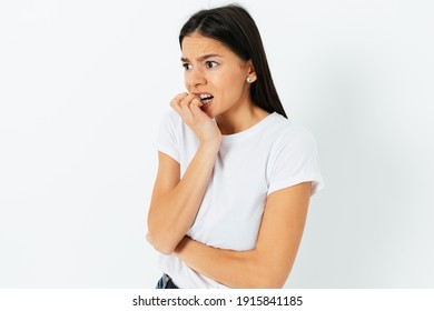 Scared anxious young woman biting nails looking to the side, standing against white studio background.
