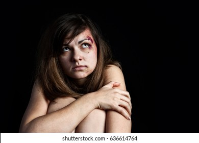 Scared beaten young woman with bruises on her face sitting on the floor and looking up. Abuse, violence concept
