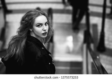 scared beautiful blond curly young woman looking back, standing on escalator, monochrome