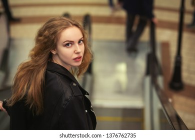 scared beautiful blond curly young woman looking back, standing on escalator