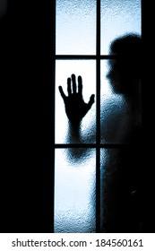 Scared boy behind glass door showing one hand