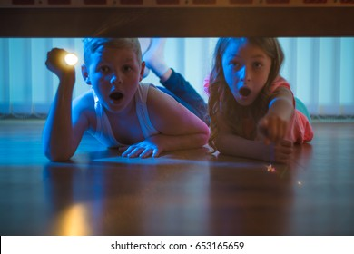 The scared boy and girl lay on the floor with a flashlight. night time