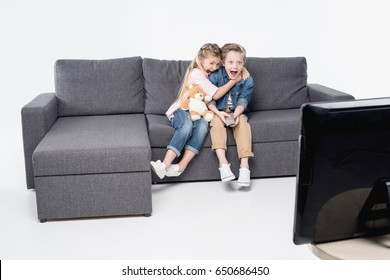 scared boy and girl sitting on sofa and watching tv together isolated on white
