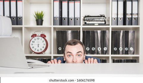 Scared business man hiding behind the table in office