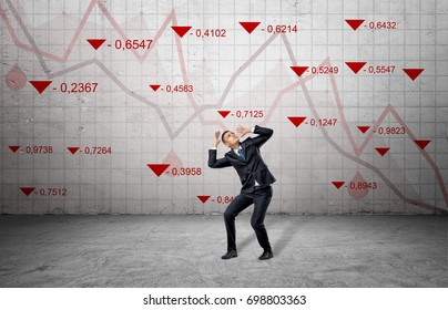 A scared businessman cowers near a concrete wall with red stock market indexes and falling statistic lines. Financial markets. Bear trading. Losing money.