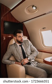 scared businessman fastening safety belt while looking in porthole of private plane