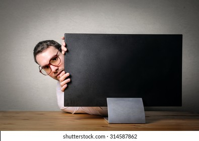 Scared businessman hiding behind a pc