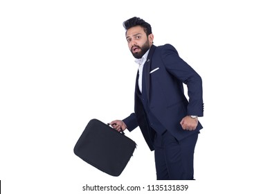 Scared businessman moving in escaping pose holds briefcase looking back isolated on a white background.