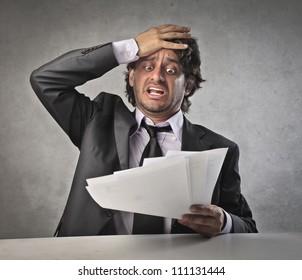Scared businessman observing some bills