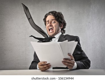 Scared businessman reading some documents