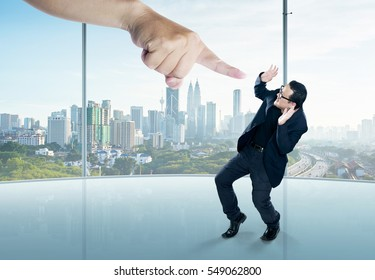 A scared businessman  in a scare pose and a giant hand pointing at him, on the office background. Business and management, employment issues or getting fired.