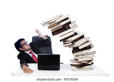 Scared businessman with stack books which about to collapse. Shot in studio isolated on white