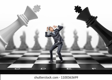 A scared businessman stands between a black and a white chess kings falling on him. Between two fires. Business problems. Strategic failure.
