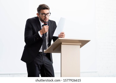 scared businessman in suit standing at podium tribune and speaking during conference isolated on white