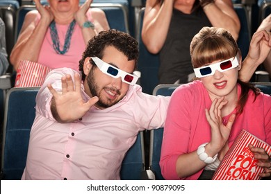 Scared Caucasian couple with 3D glasses in theater