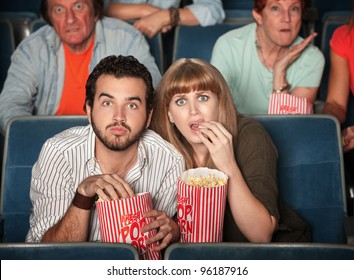 Scared Caucasian couple eating popcorn in theater