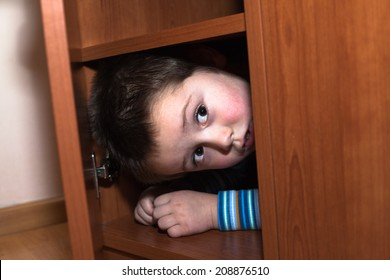 Scared child boy hiding in wardrobe