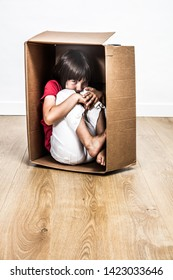 scared child hunched in a small cardboard box, seeking for a refuge from bullying, disrespect or black violent education, contrast effects