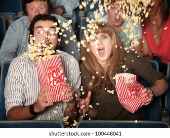 Scared couple jump in their seats with spilled popcorn