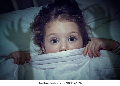scared cute little girl under the blanket in her bed. Imagination of children concept.