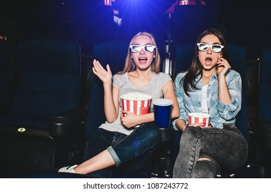 Scared and excited girls are sitting in a cinema hall and watching movie. They are amazed. Also girls have baskets of popcorn and a big cup of cola.