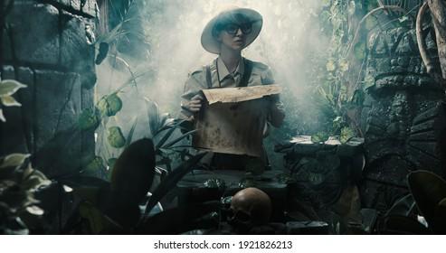 Erkundungsgefahr im Dschungel verloren: sie hält eine Karte und sieht sich einige alte Ruinen an