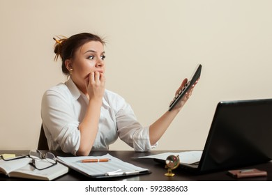 Scared female bookkeper looks at the balance sheet