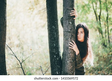 Scared girl is alone in forest is hiding behind tree trunk. Lonely girl got lost in woods in halloween. Beautiful witch escapes persecution. Female portrait in wild on background of autumn bokeh.