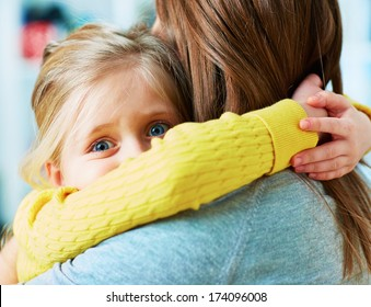 Scared girl. Daughter embrace mother. Home portrait.