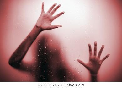 Scared girl hand behind glass door