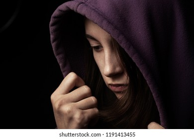 scared girl in hood looking down on black background