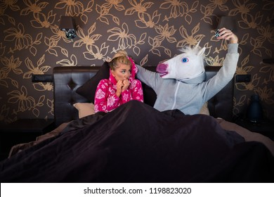 Scared girl is lying with funny boyfriend in comical mask. Unusual couple playing in adult game in the bed at the stylish bedroom.